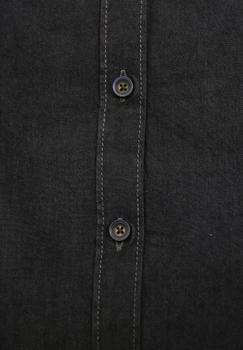 Zwarte chambray (denim look) overhemd van Melvinsi, met kleine speelse details in dezelfde bedrukte grijze stof als aan de binnenkant van de kraag, de schouderpass en de mouwen. Het overhemd heeft een button down kraag en is rond afgezoomd.